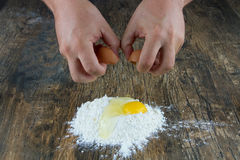 Two hands break egg on wooden surface on a heap of flour Royalty Free Stock Photos