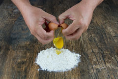 Two hands break egg on wooden surface on a heap of flour Stock Photo