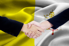 Two hands business with Vatican City flag Royalty Free Stock Image