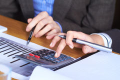 Two hands with calculator and some paperwork Stock Image