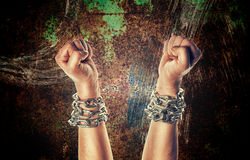 Two hands in chains. On a grunge background with scratches royalty free stock image