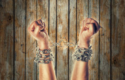 Two hands in chains. On a wooden background background with scratches Stock Photos