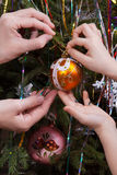 Two hands, child and women, decorating Christmas tree. Together, closeup Royalty Free Stock Images