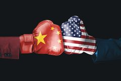 Two hands with China and USA flag. Two hands wearing boxing gloves with China and USA flag. Shot with black background royalty free stock photos