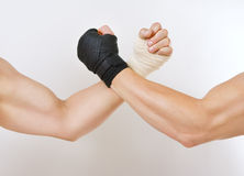 Two hands clasped arm wrestling, the struggle of black and white. Hand in a white glove and hand in a black glove clasped arm wrestling, good and evil opposition Stock Photo