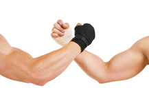 Two hands clasped arm wrestling, the struggle of black and white. Hand in a white glove and hand in a black glove clasped arm wrestling, isolated on white, good Royalty Free Stock Photos
