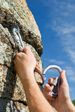 Two hands of climber fix equipment on rock Royalty Free Stock Image