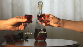 Two hands clink glasses with a liquor of red color. Two hands clink glasses with the liquor of the red color above the table with a carafe stock video footage
