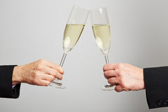 Two hands clinking champagne glasses Stock Image