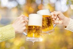 Two hands are clinking mugs with fresh foam beer . stock image