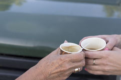 Two Hands With Coffee Cups. Two female hands, aged and young, holding cups of coffee in front of car, outdoor cropped shot Royalty Free Stock Images