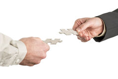 Two hands coming from opposite directions matching two puzzle pi Royalty Free Stock Photo
