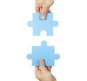 Two hands connecting puzzle pieces Stock Photography