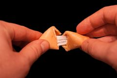 Two hands cracking a fortune cookie. Open stock photography