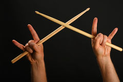 Two hands with crossed drumsticks and devil horns. Two man hands holding crossed wooden drumsticks and devil horns rock metal gesture sign over black background Royalty Free Stock Image