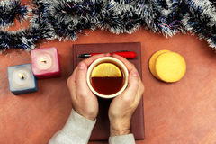 Two hands with a Cup of hot tea are on the Christmas notebook on Royalty Free Stock Photography