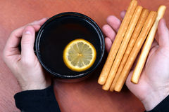 Two hands with a cup of tea and biscuits close up Royalty Free Stock Photo