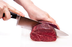 Two hands cutting a fillet of beef Stock Photos
