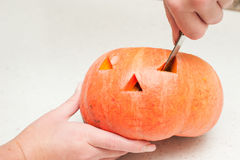 Two hands cutting pumpkin Royalty Free Stock Photos