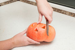 Two hands cutting pumpkin Royalty Free Stock Images