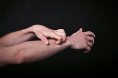 Two hands in the dark. Beautiful man`s hands on black background close up Royalty Free Stock Image