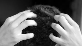 TWO HANDS DOING HAIR MASSAGE ON THE HEAD OF A CAUCASIAN MALE TEENAGER ISOLATED ON BLACK BACKGROUND.