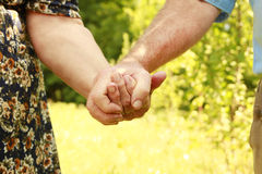 Two hands of an elderly couple Stock Photos