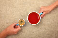 Two hands with espresso coffee and black tea cups. Different habits, two hands, man and woman, holding full cups, small espresso coffee and big black tea Stock Photos