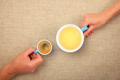 Two hands with espresso coffee and green tea cups. Different habits, two hands, man and woman, holding full cups, small espresso coffee and big green tea Stock Images
