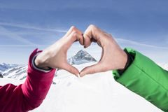 Two hands form a heart with mountains in the background stock images