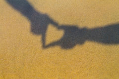 Two hands forming a heart shadow or love symbol on the beach. Holiday time. Vacation time. Stock Image