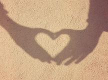 Two hands forming a heart shadow on the wall Stock Image