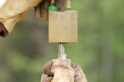 Two Hands in gloves with key and unlocked padlock. Stock Photos