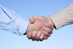 Two hands handshake isolated on sky background. Two businessmen hands handshake isolated on sky background royalty free stock photography