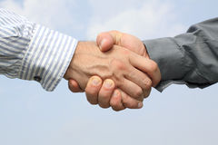 Two hands handshake on sky background. Two man hands handshake on sky background royalty free stock images