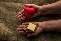 Two hands with heart on one hand and butter on other. Concept benefits and harms of butter for health.  For some, it is harmful, for other people it is Royalty Free Stock Image