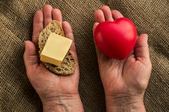 Two hands with heart on one hand and butter on other. Concept benefits and harms of butter for health.  For some, it is harmful, for other people it is Stock Images