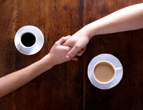 Two hands held together with cups of coffee Royalty Free Stock Photo
