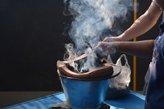 Two hands helped kindled a fire in charcoal stove and smoke floa Stock Photo