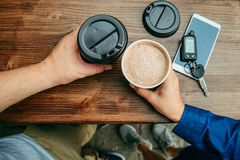 Two hands hold cups of coffee on the wooden table Royalty Free Stock Photo