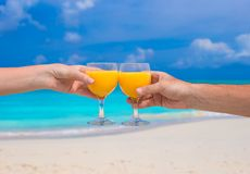 Two hands hold glasses with orange juice background blue sky Stock Images