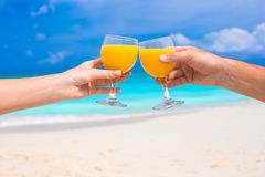 Two hands hold glasses with orange juice background blue sky Stock Photo