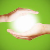 Two hands hold a glowing light or sun. As symbol for meditation or pray Royalty Free Stock Photo