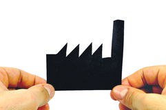 Two Hands holding a black paper factory shaped. On a white background Stock Photo