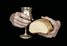 Two hands holding bread and wine for communion, isolated on black. Two male hands holding bread and wine for Holy communion isolated on a black background royalty free stock images