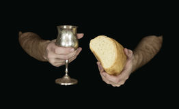 Two hands holding bread and wine for communion, isolated on black. Two male hands holding bread and wine for Holy communion isolated on a black background royalty free stock image