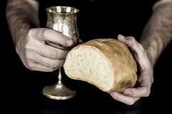 Two hands holding bread and wine for communion, isolated on black. Two male hands holding bread and wine for Holy communion isolated on a black background royalty free stock photo