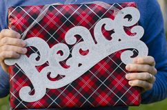 Two hands holding a Christmas peace sign and Christmas present. Royalty Free Stock Image
