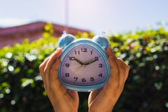 Two Hands holding Clock against leaves Stock Photo