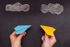 Two hands holding two colorful paper planes under clouds stock images
